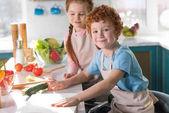 Fotografie schöne, glückliche Kinder in Schürzen, gemeinsames Kochen in der Küche