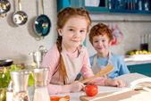 Fotografie entzückende Kinder Lächeln in die Kamera während des Cookign zusammen in der Küche