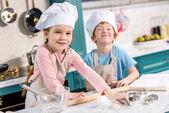 Fotografie entzückende kleine Kinder in Kochmützen und Schürzen lächelnd in die Kamera beim Kochen zusammen in Küche