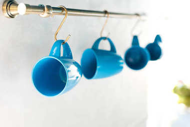 selective focus of empty blue cups hanging in kitchen