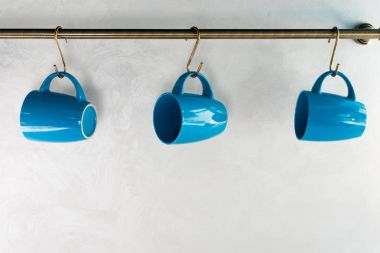 close-up view of empty blue cups hanging in kitchen