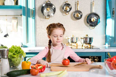adorable little child in apron cooking in kitchen