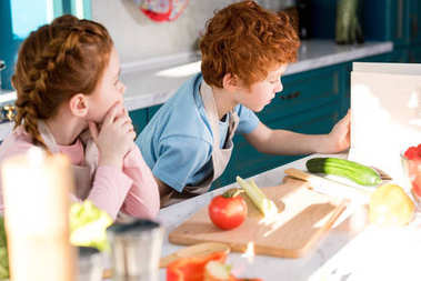 children in aprons reading coobook while preparing vegetable salad together in kitchen