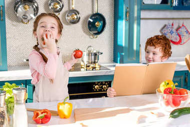 little boy holding cookbook while adorable child eating tomato in kitchen