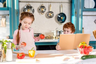 children with cookbook and vegetables cooking together in kitchen