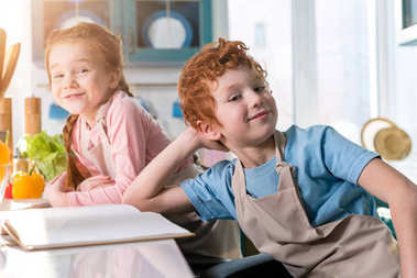 adorable kids in aprons smiling at camera while cooking with cookbook in kitchen