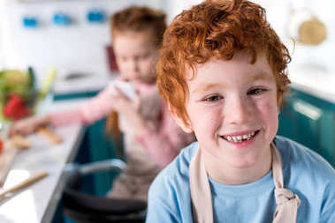 cute little boy smiling at camera while friend cooking behind in kitchen