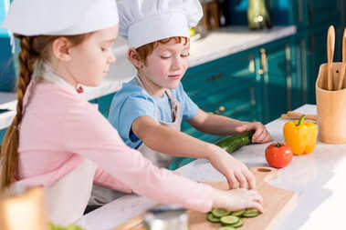 cute kids in chef hats and aprons preparing vegetable salad together in kitchen
