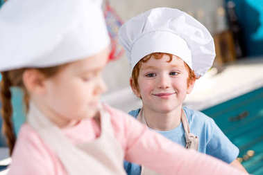 adorable smiling little boy in chef hat looking at friend cooking on foreground