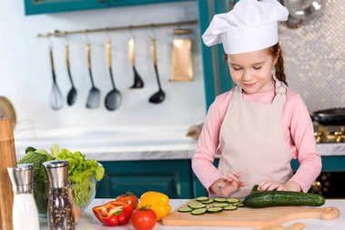 smiling kid in chef hat and apron cooking vegetable salad in kitchen