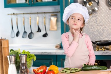 thoughtful kid in chef hat and apron looking away in kitchen