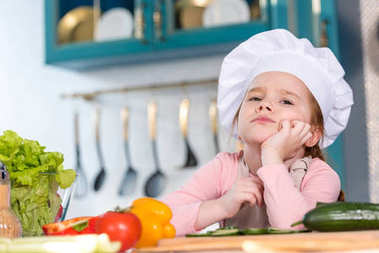 bored child in chef hat sitting with hand on chin in kitchen