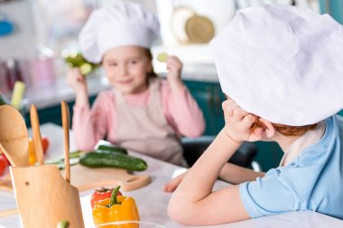 adorable children in chef hats looking at each other while cooking together in kitchen