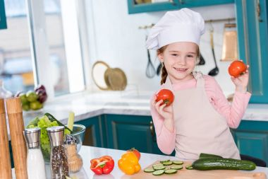 cute child in chef hat and apron holding tomatoes and smiling at camera while cooking in kitchen