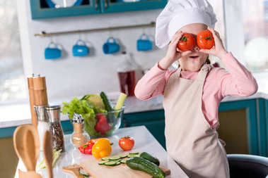 cute child in chef hat and apron holding tomatoes while cooking in kitchen