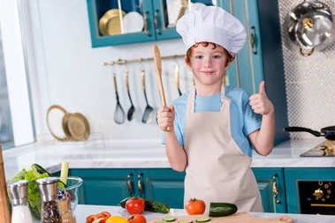 cute little boy in chef hat and apron smiling at camera and showing thumb up in kitchen