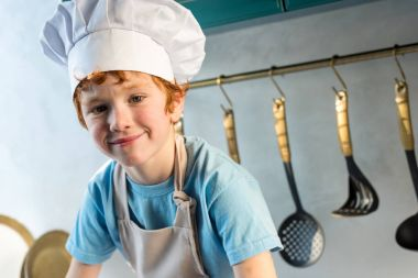 adorable little boy in chef hat and apron smiling at camera in kitchen