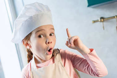 cute child in chef hat pointing up with finger and looking at camera in kitchen