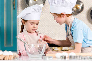 beautiful little children in chef hats and aprons cooking together in kitchen