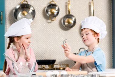 adorable children in chef hats and aprons cooking together in kitchen