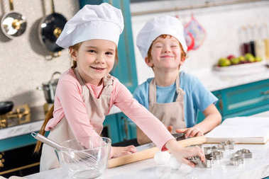 adorable little kids in chef hats and aprons smiling at camera while cooking together in kitchen