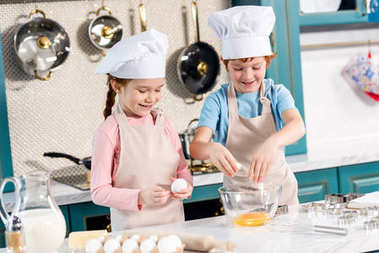 cute smiling kids in chef hats and aprons preparing dough together in kitchen