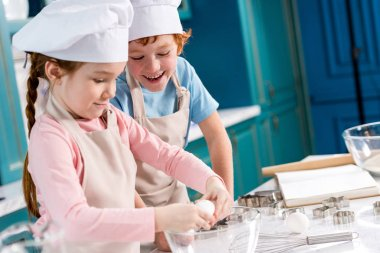 adorable happy little kids in chef hats and aprons making dough together in kitchen