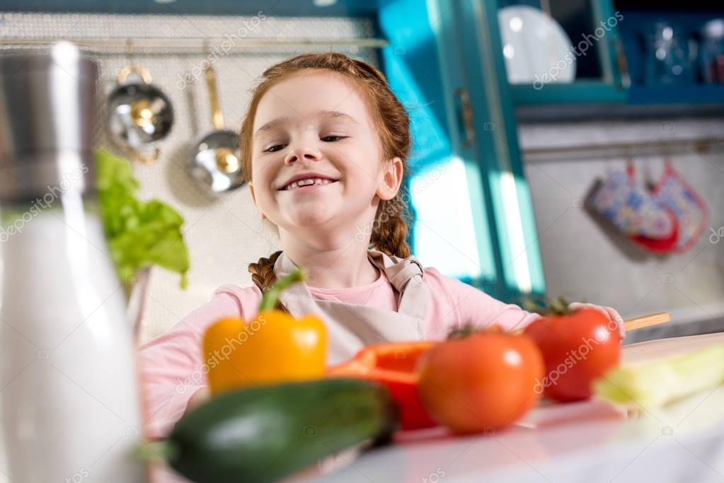 adorable little child smiling while cooking in kitchen