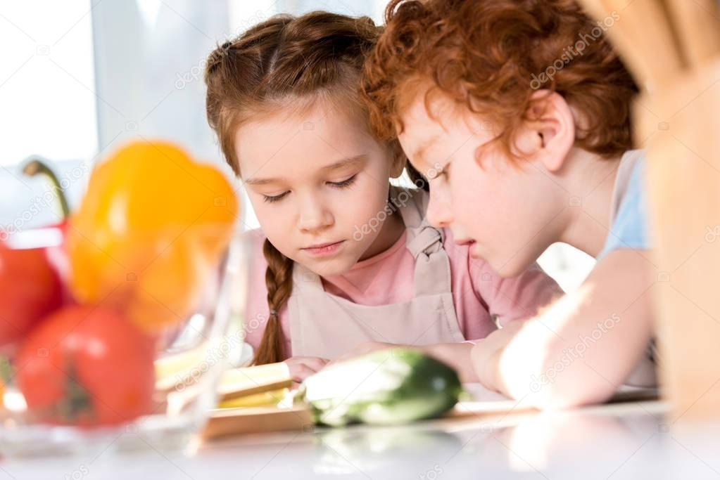 focused children reading cookbook while cooking together in kitchen