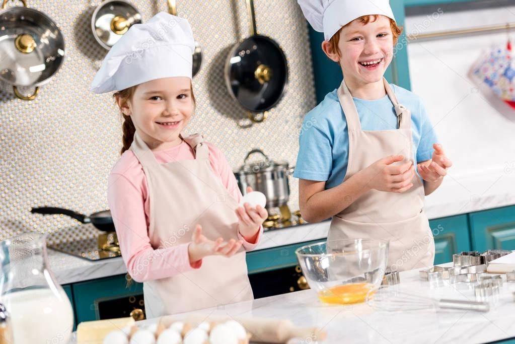 adorable happy children in chef hats and aprons smiling at camera while making dough together in kitchen