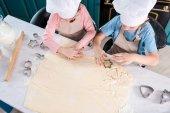 Fotografie Draufsicht der Kinder in Kochmützen Cookies gemeinsam vorbereiten