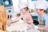 Fotografie glückliche kleine Kinder Koch Hut Vorbereitung Cookies zusammen in der Küche