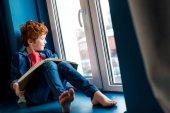 roztomilý bosý chlapec s knihou sedět na parapetu