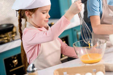 child in chef hat and apron whisking eggs in kitchen