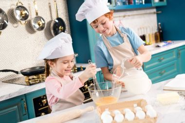 happy little kids in chef hats and aprons preparing dough together in kitchen