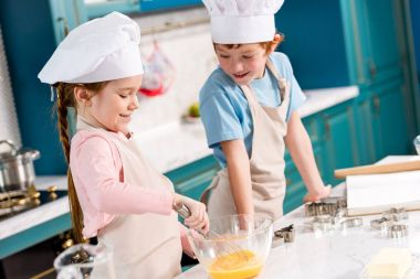 adorable smiling children in chef hats and aprons making dough together in kitchen