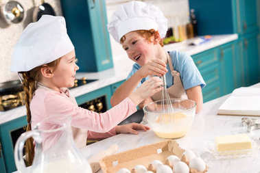 cute little kids in chef hats smiling each other while whisking dough in kitchen