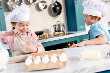 happy little children in chef hats and aprons making dough in kitchen