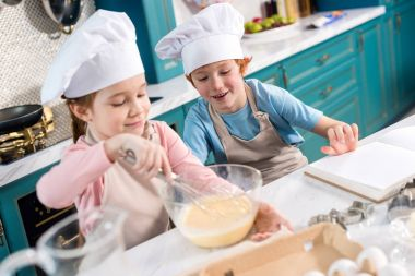 happy children in chef hats making dough in kitchen
