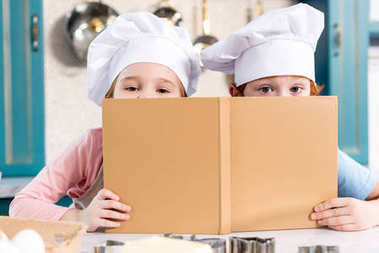 cute children in chef hats holding cookbook and looking at camera