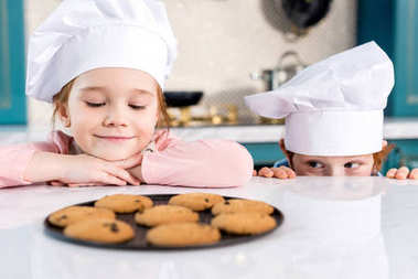 adorable happy kids in chef hats looking at tasty cookies on table
