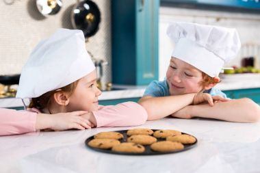 happy children in chef hats smiling each other and delicious cookies on table