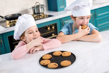 happy children in chef hats eating tasty cookies in kitchen