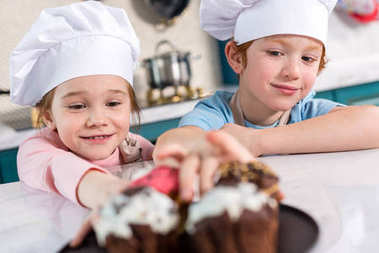 smiling little children in chef hats looking at delicious cupcakes on foreground