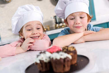 happy kids in chef hats looking at delicious cupcakes on foreground