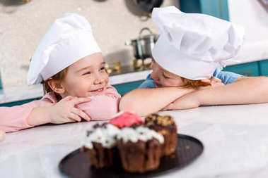 adorable kids in chef hats smiling each other and delicious cupcakes on foreground