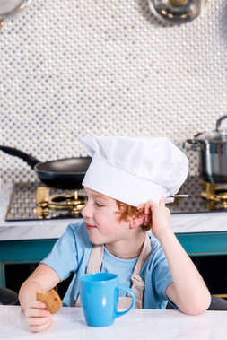 cute little boy in chef hat drinking tea and eating cookie in kitchen
