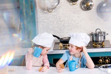 cute little kids in chef hats drinking tea and eating cookies in kitchen