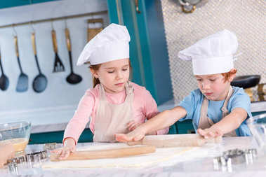 cute little kids preparing dough for cookies in kitchen