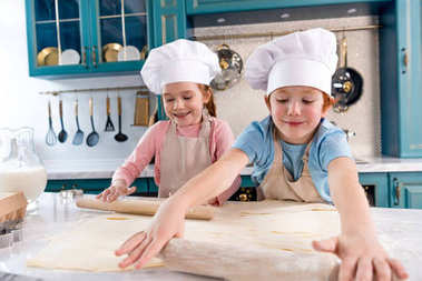 happy little kids in chef hats and aprons rolling dough in kitchen